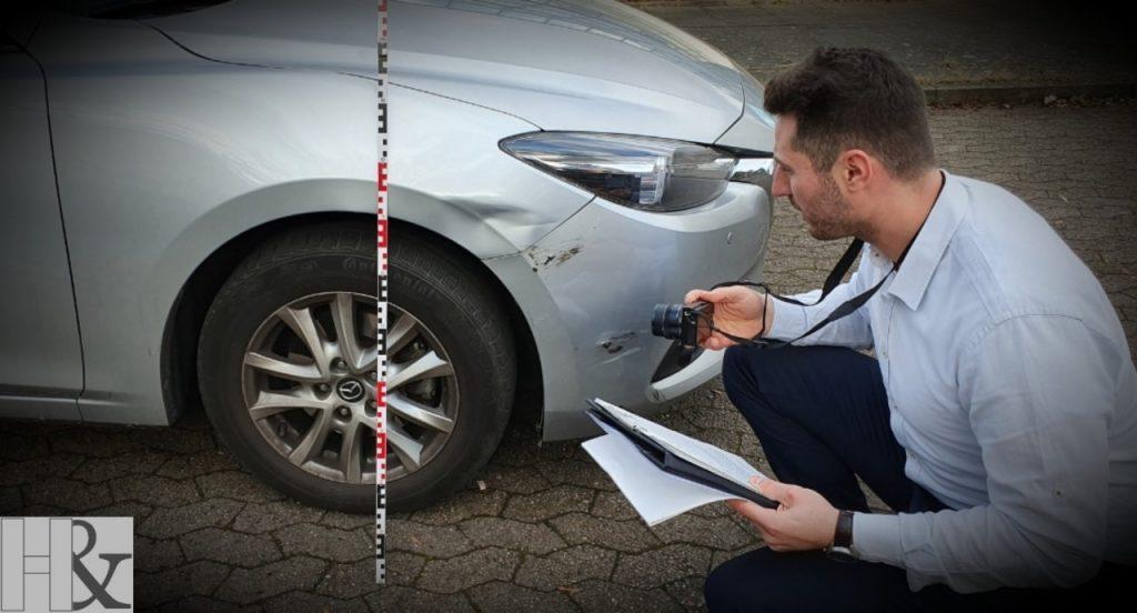 Gutachter am Fahrzeug zur Betrachtung der Schäden